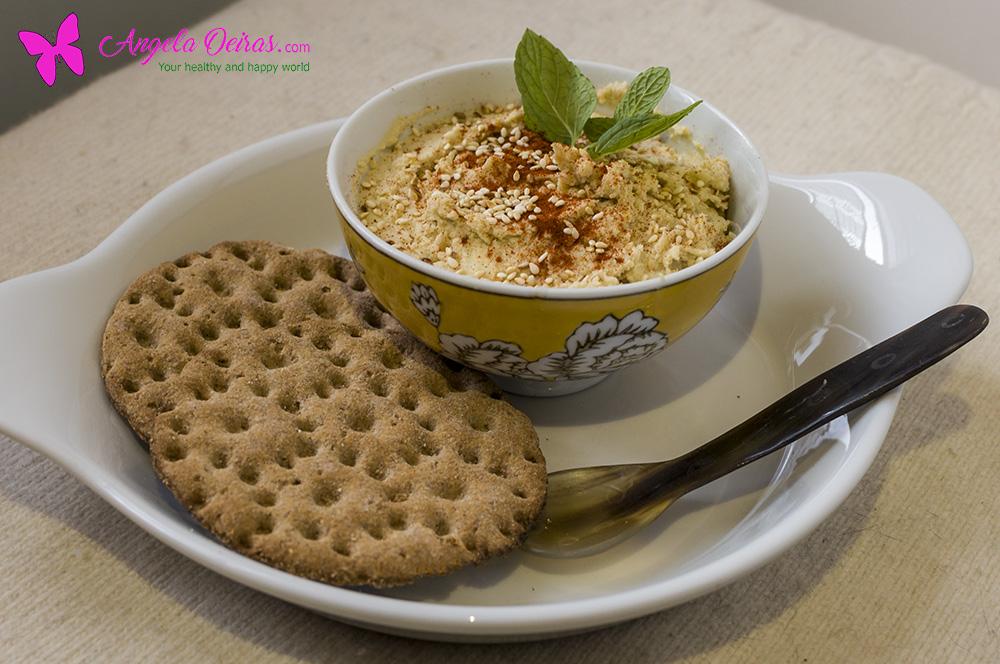 Taça com húmus de batata doce decorada com pimentão doce e folhas de hortelã e acompanha com tostas