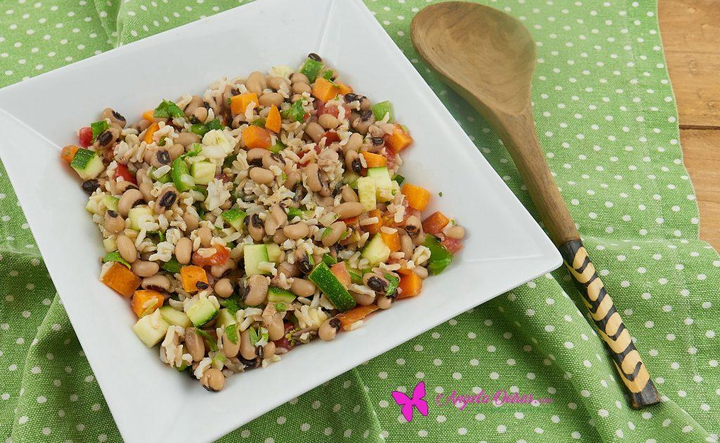 prato de salada de feijão com arroz e legumes, pano verde e colher de madeira